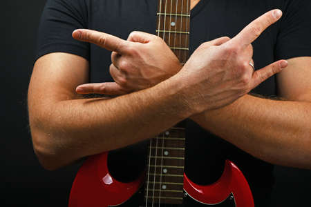 sg: Man hands holding embracing red sg guitar neck with devil horns rock metal sign over black background Stock Photo