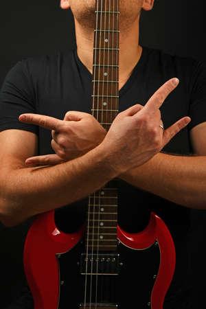 sg: Man holding embracing red sg guitar neck with two hands showing devil horns rock metal sign over black background