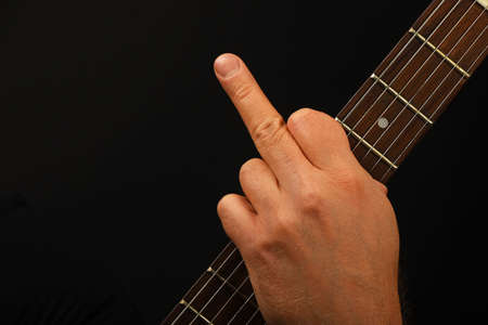 insult: Man hand holding guitar neck with finger fuck off insult ignore gesture over black background