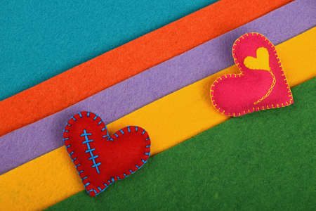 stitched: Craft and art, two handmade stitched toy hearts, pink and red on colorful felt diagonal stripes background