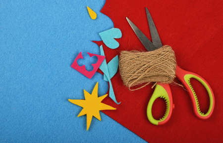 art and craft: Craft and art, felt pieces, cuts, jute twine thread bobbin and scissors on red and blue background Stock Photo