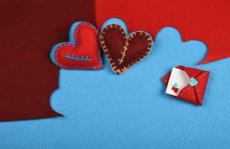 stitched: Felt craft and art, two handmade stitched toy hearts, brown and red cut out on blue felt background, with letter envelope