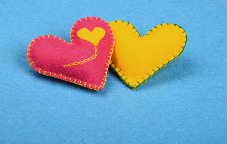 stitched: Felt craft and art, two handmade stitched toy hearts, pink and yellow together on blue background