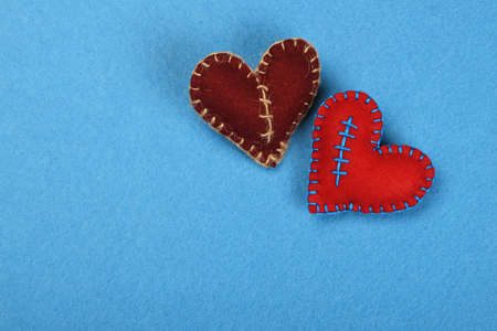 stitched: Felt craft and art, two handmade stitched toy hearts, red and brown together on blue background Stock Photo