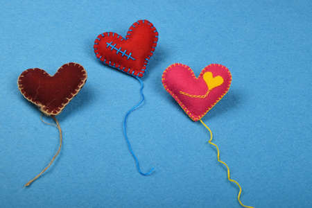 stitched: Felt craft and art, three handmade stitched toy hearts with threads, red, pink and brown on blue background