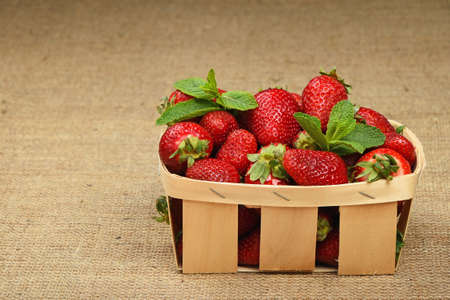 mellow: Wicker wooden basket full of mellow red summer strawberries and fresh mint leaves on jute burlap canvas background, side view Stock Photo