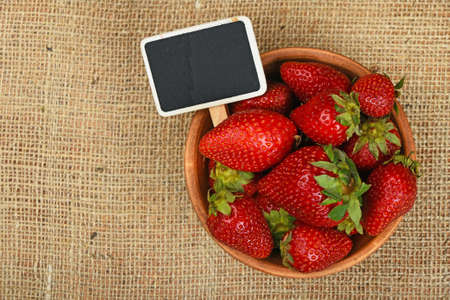 mellow: Fresh mellow red strawberries in rustic ceramic bowl with chalk blackboard price tag sign on jute burlap canvas background, top view