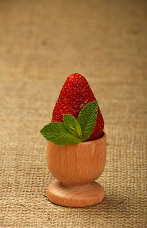 mellow: One big red mellow strawberry and green fresh mint leaves in wooden eggcup holder on natural burlap jute canvas background