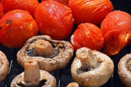 Vegetables in salt and spices being cooked on char grill, white champignons portobello mushrooms and red small tomatoes Stock Photo