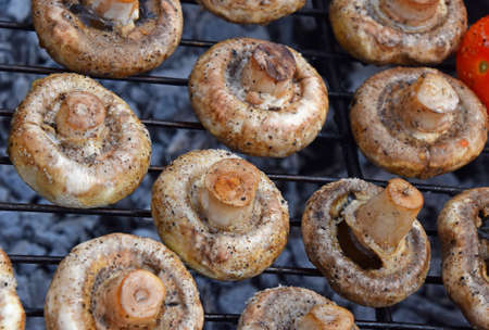 char: White champignons portobello mushrooms being cooked on char grill, close up Stock Photo