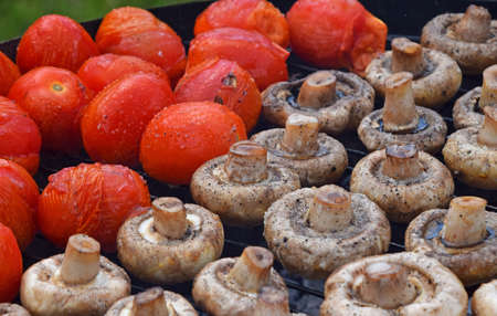 char: Vegetables in salt and spices being cooked on char grill, white champignons portobello mushrooms and red small tomatoes Stock Photo