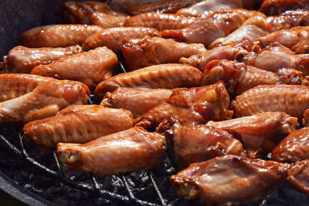 sizzle: Chicken buffalo or teriyaki sauce raw wings cooked grilled on bbq smoke round grill, close up