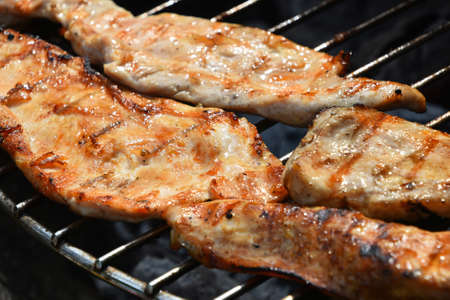 sizzle: Chicken or turkey meat barbecue steak ready cooked grilled on bbq smoke grill, close up