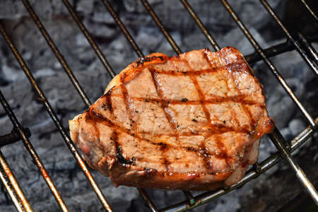 One beef or pork meat barbecue steak ready cooked grilled on bbq smoke grill, close up