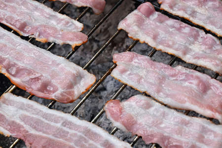 sizzle: Raw smoked melting grilled barbecue bacon slices, being cooked on bbq smoke grill, close up Stock Photo