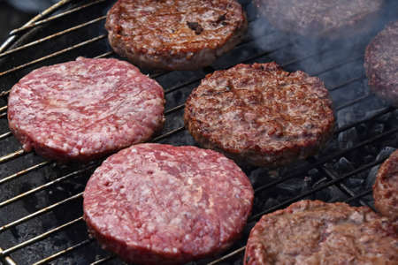 Raw and medium rare cooked beef or pork meat barbecue burgers for hamburger prepared grilled on bbq smoke grill, close up