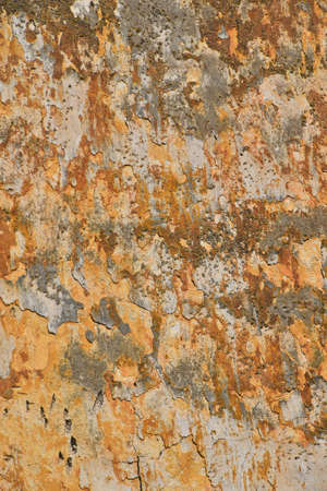 scaling: Dirty grunge grey wall with scaling peeling plaster and rusty brown stains, sags and cracks, texture background