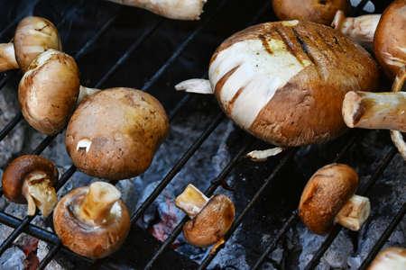 portobello: Brown champignons portobello mushrooms being cooked on char grill Stock Photo
