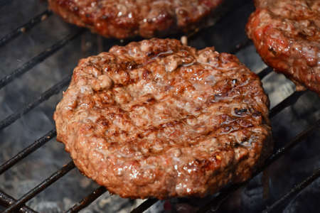 Beef or pork meat barbecue well done burgers for hamburger prepared grilled on bbq smoke grill, close up Stock Photo