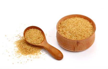 pinch: Wooden scoop spoon and bowl full of brown cane sugar with pinch of sugar spilled around isolated on white background Stock Photo