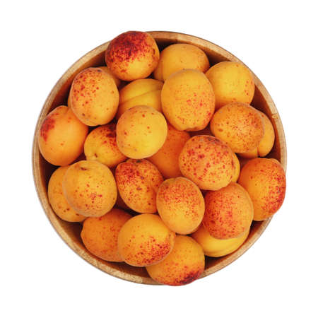 mellow: Mellow ripe fresh apricots with in big wooden bowl isolated on white background, close up, top view