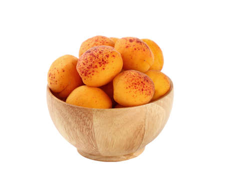 mellow: Mellow ripe fresh apricots with in small wooden bowl isolated on white background, close up