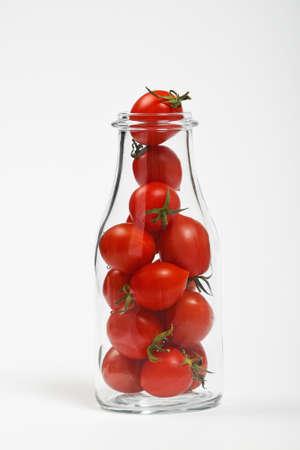 tomate cherry: Gran botella de vidrio llena de tomates cherry sobre fondo blanco como símbolo de jugo orgánico natural fresca o ketchup