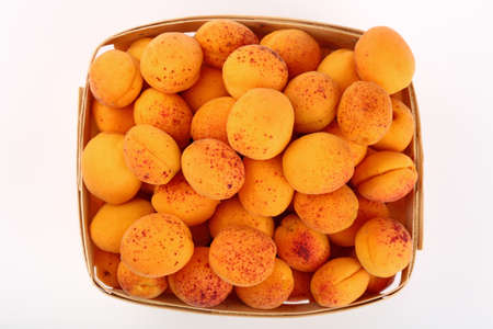 mellow: Fresh ripe mellow apricots in wooden wicker basket crate isolated on white background, close up, top view Stock Photo