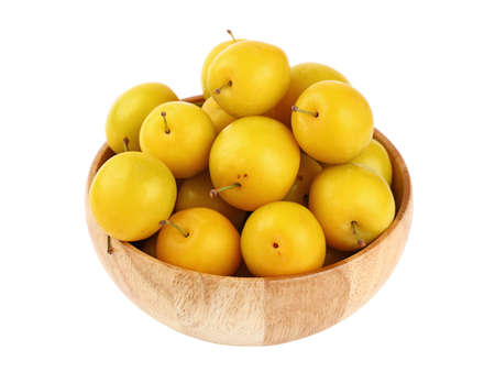 mellow: Mellow ripe fresh yellow cherry plums in wooden bowl isolated on white background, close up, high angle view