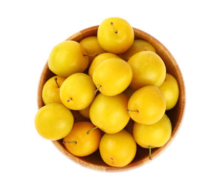 mellow: Mellow ripe fresh yellow cherry plums in wooden bowl isolated on white background, close up, top view
