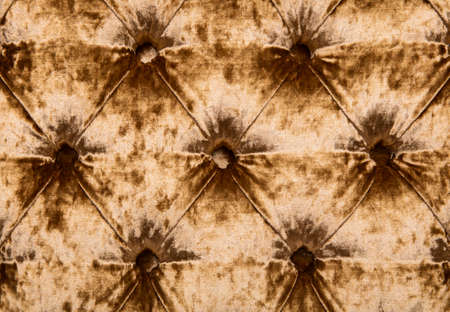button tufted: Golden velvet capitone textile background, retro Chesterfield style checkered soft tufted fabric furniture luxury decoration with buttons, close up Stock Photo