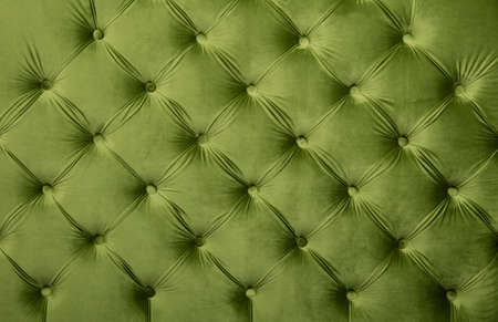 Green velvet capitone textile background, retro Chesterfield style checkered soft tufted fabric furniture diamond pattern decoration with buttons, close up Standard-Bild