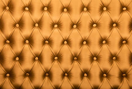 chesterfield: Golden orange capitone textile background, retro Chesterfield style checkered soft tufted fabric furniture diamond pattern decoration with buttons, close up