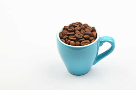 personal perspective: One small blue espresso cup full of roasted coffee beans over white background, close up, high angle view, personal perspective