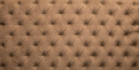 button tufted: Brown beige velvet capitone textile background, retro Chesterfield style checkered soft tufted fabric furniture diamond pattern decoration with buttons, close up