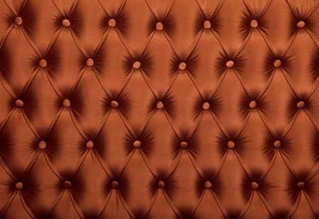 button tufted: Brown capitone textile background, retro Chesterfield style checkered soft tufted fabric furniture diamond pattern decoration with buttons, close up