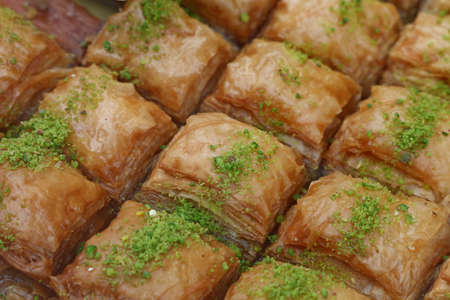 Baklava, traditional oriental sweet square pastry cookies with pistachio in retail market display, close up, high angle view