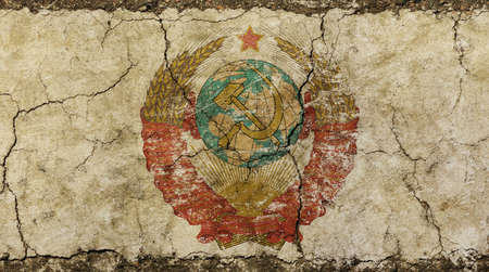cold war: Old vintage faded shabby distressed former USSR Soviet Union state emblem, coat of arms on background of grunge dirty wall with cracks and fractures