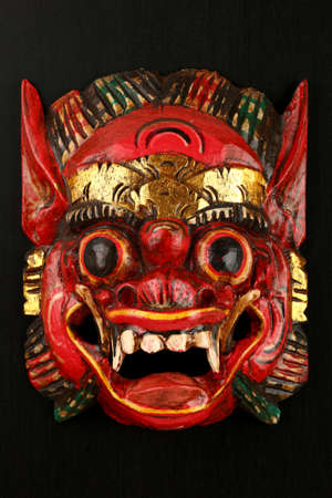Asian traditional wooden red painted mask with face of demon, mythical lion or dragon painted on black background