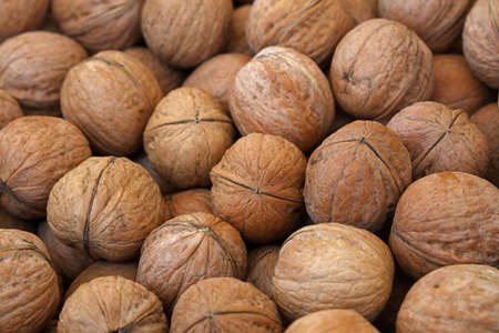nutshells: Whole walnuts with brown nutshells on retail market, close up, background, low angle view
