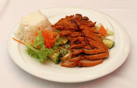 personal perspective: Peking duck Chop Suey with steamed rice and fresh vegetable salad on white plate, the meal of Chinese cuisine, close up, high angle view, personal perspective