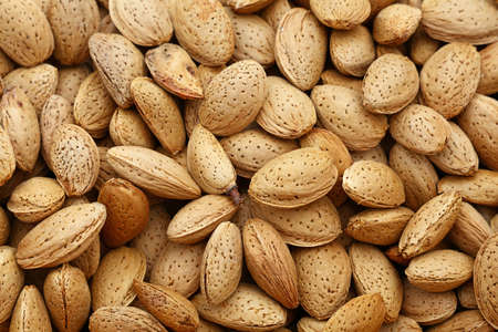 nutshells: Whole raw almond nuts with brown nutshells on retail market, close up, background, high angle, elevated top view