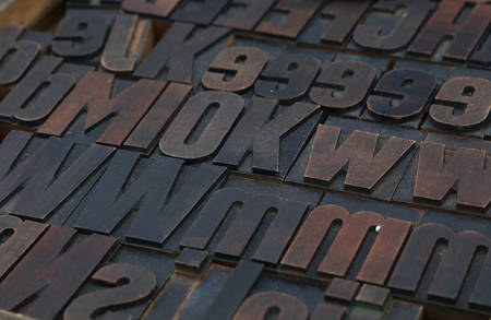 offset up: Old dark wooden vintage antique offset typography letterpress printing blocks grunge dirty with paint, mixed alphabet, close up, high angle view Stock Photo
