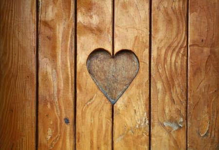 1 つのハート、愛とロマンス、木材彫刻ヴィンテージ古いグランジのテクスチャの背景の自然の茶色の木製の板、カットのシンボルをクローズ アッ