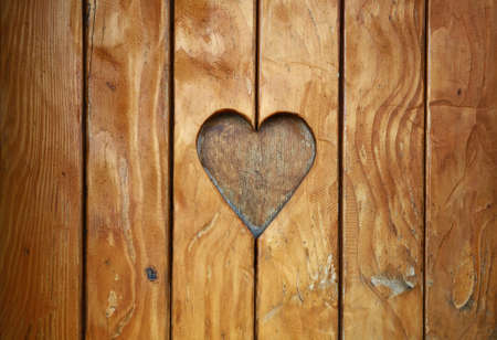 One heart shape, symbol of love and romance, wood carved cut in vintage old grunge natural brown wooden planks texture background, close up