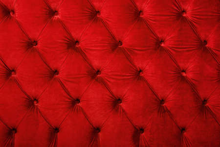 button tufted: Red velvet capitone textile background, retro Chesterfield style checkered soft tufted fabric furniture diamond pattern decoration with buttons, close up