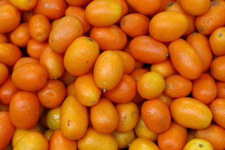 Fresh ripe orange cumquat citrus fruits on retail market display, close up, high angle view