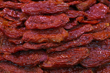 Sundried cured red tomatoes on retail fresh food market stall display, close up, low angle view