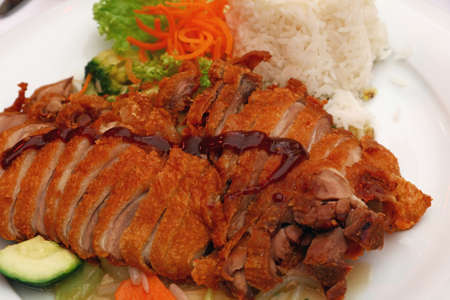 personal perspective: Peking duck Chop Suey with steamed rice and fresh vegetable salad, the meal of Chinese cuisine, close up, high angle view, personal perspective Stock Photo