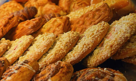 bakery store: Selection of freshly baked golden brown sweet pastry cookies in retail bakery store display, close up, high angle view Stock Photo